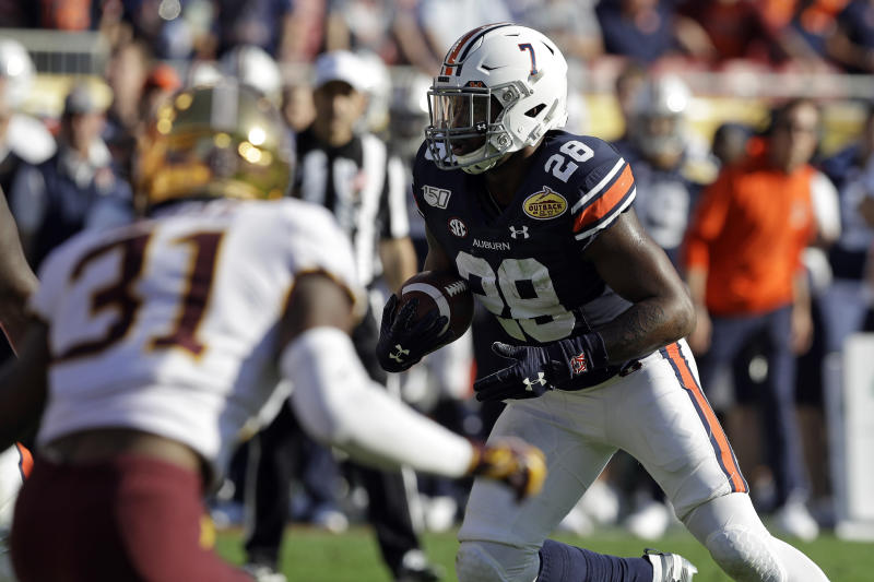 Auburn running back JaTarvious Whitlow (28) scores on a 3-yard touchdown run against Minnesota during the second half of the Outback Bowl NCAA college football game Wednesday, Jan. 1, 2020, in Tampa, Fla. (AP Photo/Chris O'Meara)