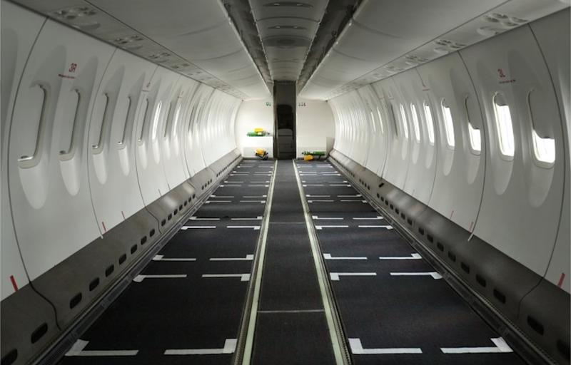 An inside view of an empty aeroplane stripped of its seats.