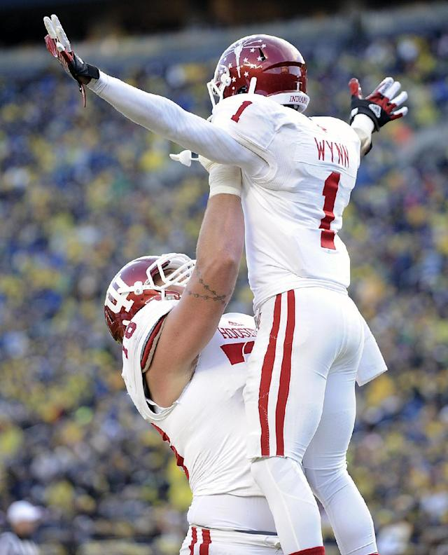Indiana wide receiver Shane Wynn, right, gets lifted into the air by offensive lineman Jason Spriggs after catching a touchdown pass in the third quarter of their NCAA football game against Michigan at Michigan Stadium in Ann Arbor, Saturday, Oct. 19, 2013. Michigan won 63-47. (AP Photo/Lon Horwedel)