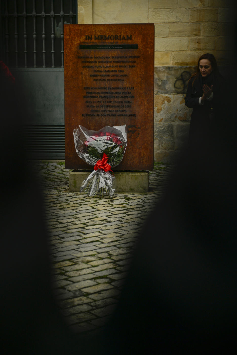 Spanish Basque socialist applauds near to a sculpture with a bunch of red roses in tribute for people killed during the Spanish Civil War, on the day that the remains of late Spanish dictator Francisco Franco are exhumed, in the basque city of Vitoria, northern Spain, Thursday, Oct. 24 2019. Forty-four years after his demise, the remains of Spanish dictator Gen. Francisco are to be dug out of his grandiose resting place outside Madrid and taken to a small family crypt, finally satisfying a long-standing demand of his victims' relatives and others who suffered under his regime. (AP Photo/Alvaro Barrientos)