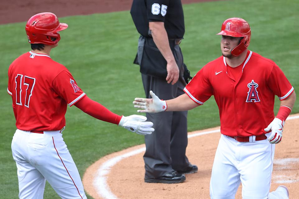 TEMPE, ARIZONA - MARCH 16: Shohei Ohtani #17 and Mike Trout #27 of the Los Angeles Angels high five after scoring off an error by Amed Rosario #1 of the Cleveland Indians in the first inning during the MLB spring training baseball game at Tempe Diablo Stadium on March 16, 2021 in Tempe, Arizona. (Photo by Abbie Parr/Getty Images)