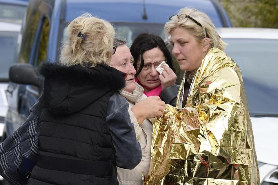 TOPSHOTS People comfort a survivor near the site of a collision on October 23, 2015 in Puisseguin where at least 43 people, most of them elderly, were killed when a coach collided with a lorry and caught fire (AFP Photo/Jean-Pierre Muller)