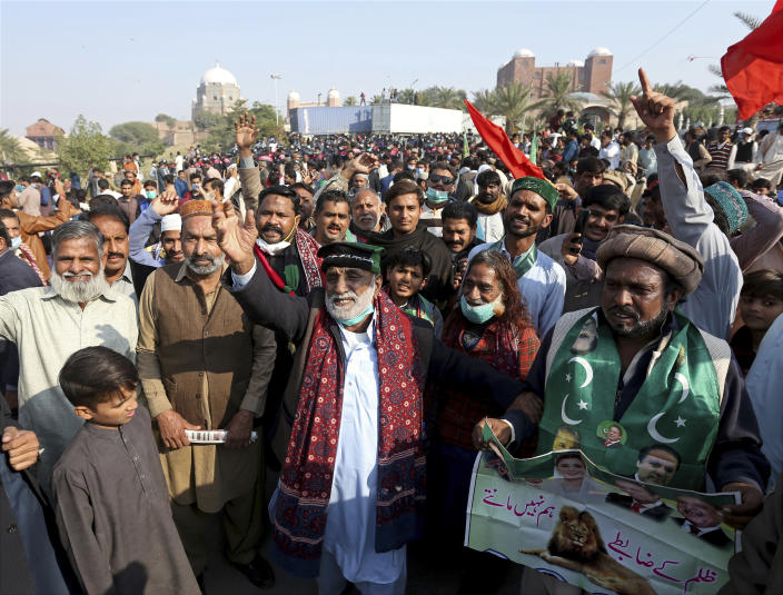 Supporters of the Pakistan Democratic Movement, an alliance of opposition parties, gather at a main intersection before an anti-government rally in Multan, Pakistan, Monday, Nov. 30, 2020. Pakistani police arrested hundreds of supporters of opposition parties ahead of a planned rally Monday calling for the country's prime minister to resign, a move the government defended as necessary to combat the coronavirus pandemic. (AP Photo/Asim Tanveer)
