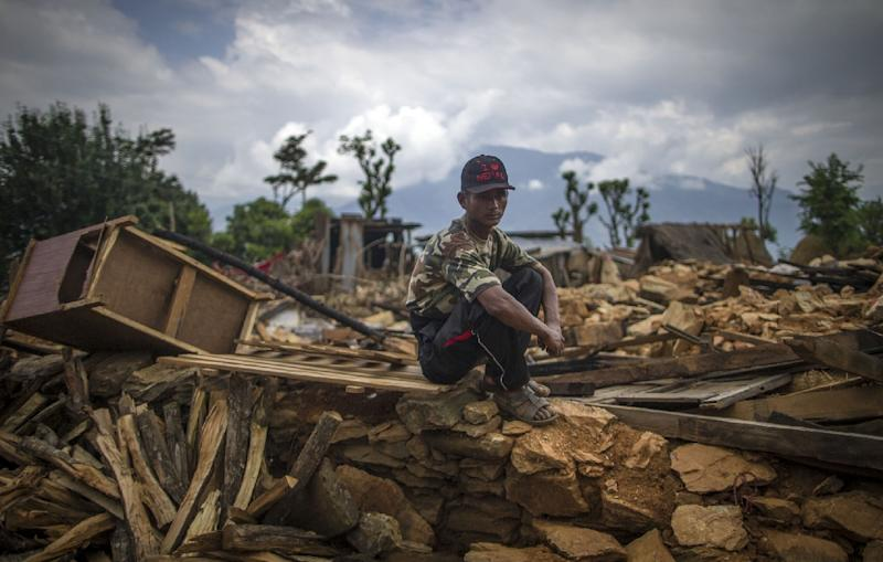 A man sitting on in the ruins of damaged houses in Paslang village in Gorkha, Nepal, April 30, 2015