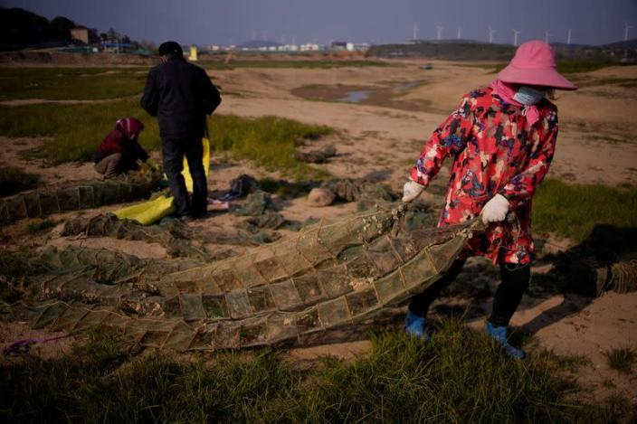 FILE PHOTO: Fishermen recycle shrimp nets on the dried lake bed of Poyang lake, China