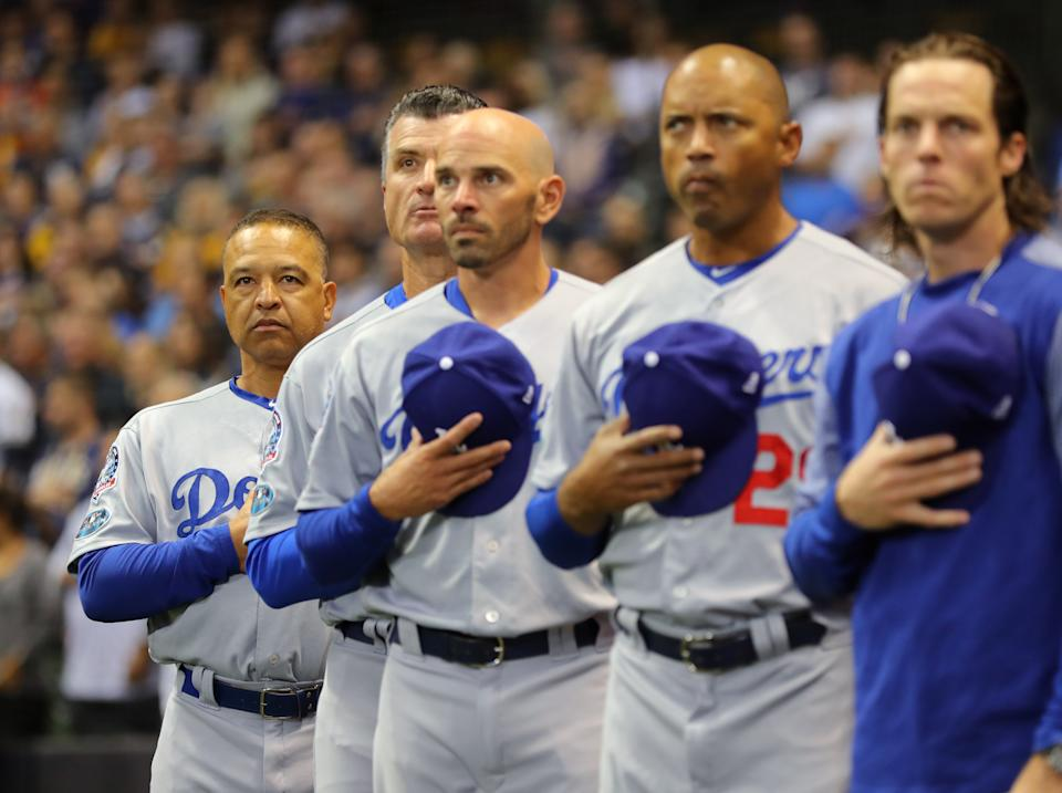 MILWUAKEE, WI - OCTOBER 19:  Manager Dave Roberts #30, Bob Geren #16, Chris Woodward #45, George Lombard #29 and Danny Lehmann #0 of the Los Angeles Dodgers stand on field for the national anthem before Game 6 of the NLCS against the Milwaukee Brewers at Miller Park on Friday, October, 19, 2018 in Milwaukee, Wisconsin. (Photo by Alex Trautwig/MLB via Getty Images)