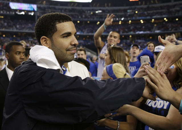Canadian entertainer Drake greets Kentucky fans during halftime of an NCAA Final Four tournament college basketball semifinal game against Wisconsin Saturday, April 5, 2014, in Arlington, Texas. (AP Photo/David J. Phillip)