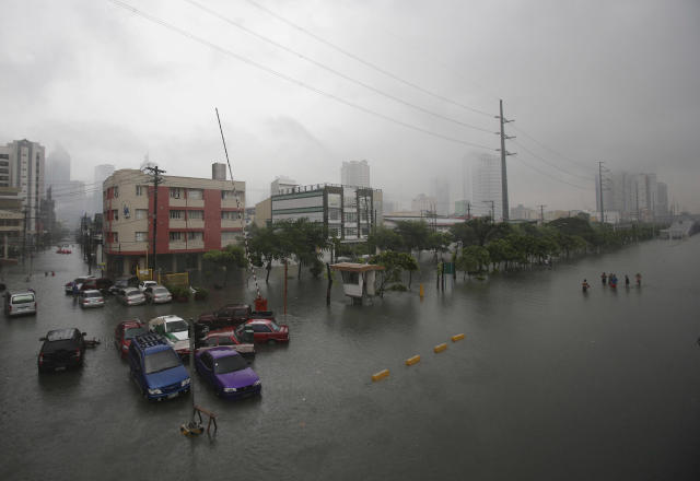 Vehicles are parked along a flooded area at the financial district of Makati, south of Manila, Philippines on Tuesday, Aug. 20, 2013. Some of the Philippines' heaviest rains on record fell for a second day Tuesday, turning the capital's roads into rivers and trapping tens of thousands of people in homes and shelters. The government suspended all work except rescues and disaster response. (AP Photo/Aaron Favila)