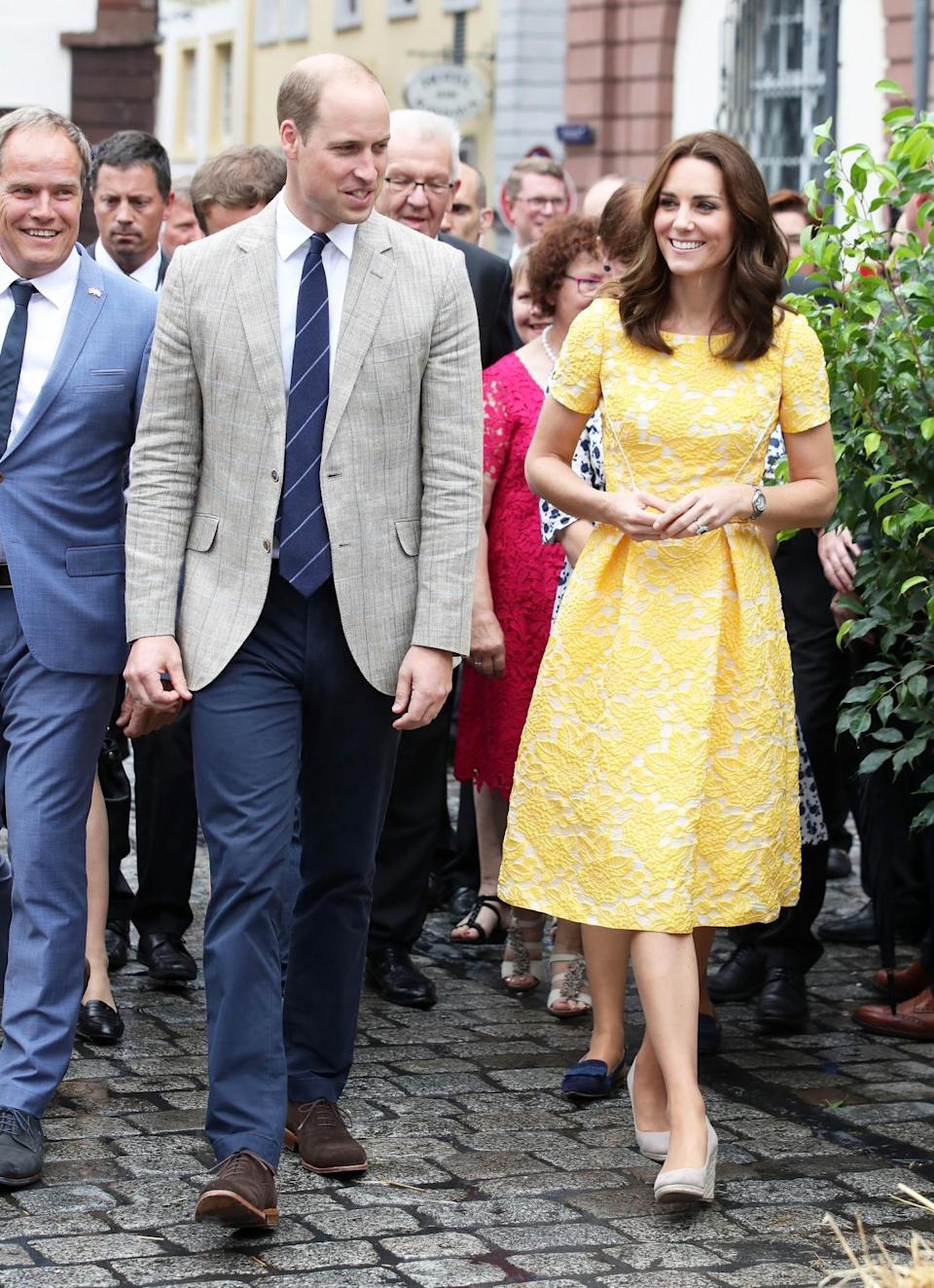 <p><b>For a visit to a German market, Kate wore a bespoke lemon dress by British favourite Jenny Packham. Monsoon wedges and statement Oscar de la Renta earrings completed the look. <br><em>[Photo: PA]</em> </b></p>