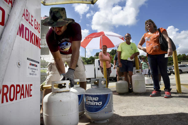 <p>Gustavo Galindo, left, fills propane tanks at an Exxon gas station in Davie, Fla., Thursday, Sept. 7, 2017, as a long line of people wait in line as residents prepare for Hurricane Irma. (Photo: Taimy Alvarez/South Florida Sun-Sentinel via AP) </p>