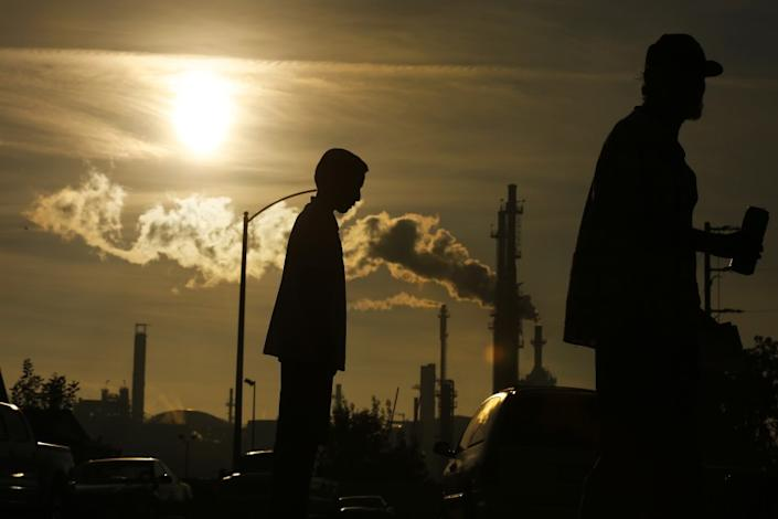 """A boy and his grandfather stand near the Phillips 66 refinery in Wilmington. <span class=""""copyright"""">(Los Angeles Times)</span>"""