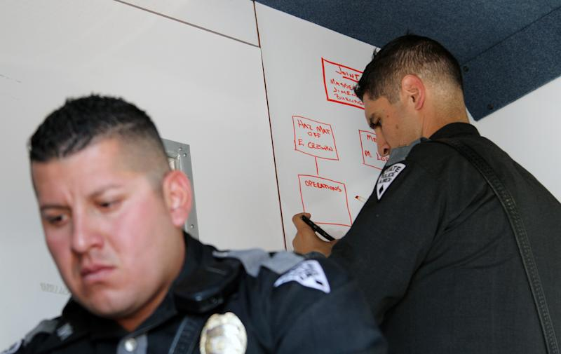 New Mexico Police officer Armando Reyes uses a computer while Lt. Roman Jimenez writes on a whiteboard at the command center outside the Santa Teresa Industrial Park, Tuesday, Oct. 30, 2012 in Santa Teresa, N.M. New Mexico authorities say an unknown hazardous materials release has sickened about 200 people near the Mexican border just northwest of El Paso, Texas. (AP Photo/Juan Carlos Llorca)