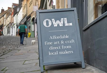 An independent shop advertising board is seen in one of the older commercial streets in Frome