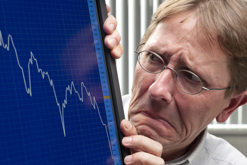 A visibly worried investor looking at a plunging stock chart on his computer monitor.