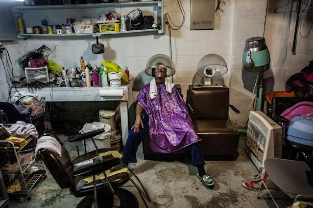 "<p>Olympic Gold Medal Boxer Claressa ""T-Rex"" Shields finishes having her hair done in the basement studio of Miss Paula, a women that she once lived with in Flint. Claressa has lived all over Flint, with a grip of different people but she is now fairly settled in with her coach Jason Crutchfield. (Photograph by Zackary Canepari) </p>"