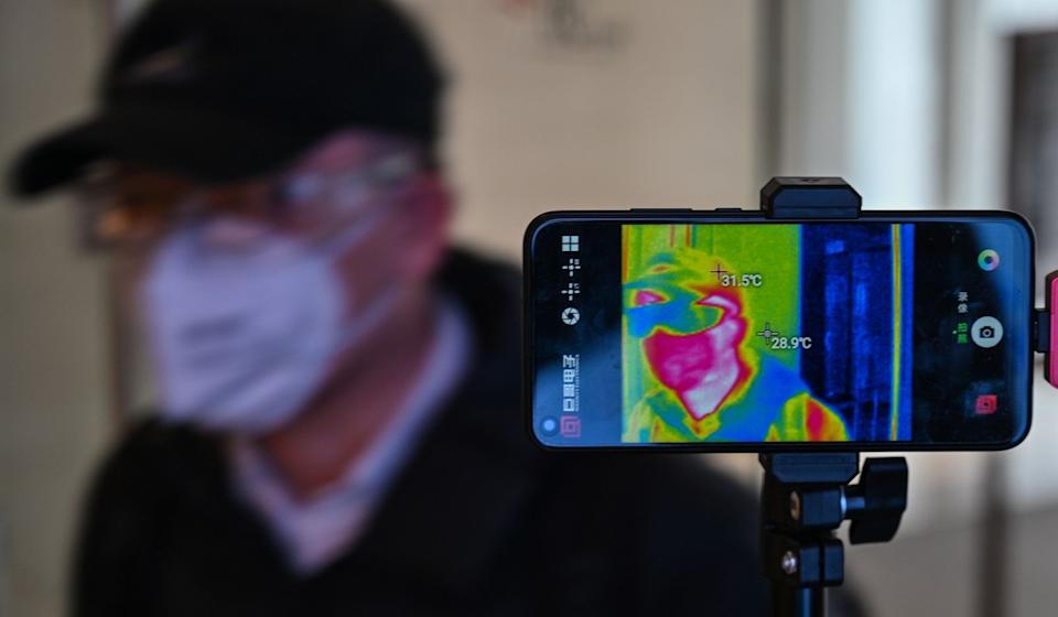 A man wearing a face mask has his temperature measured in at a shopping centre in Shanghai on Wednesday. Photo: AFP