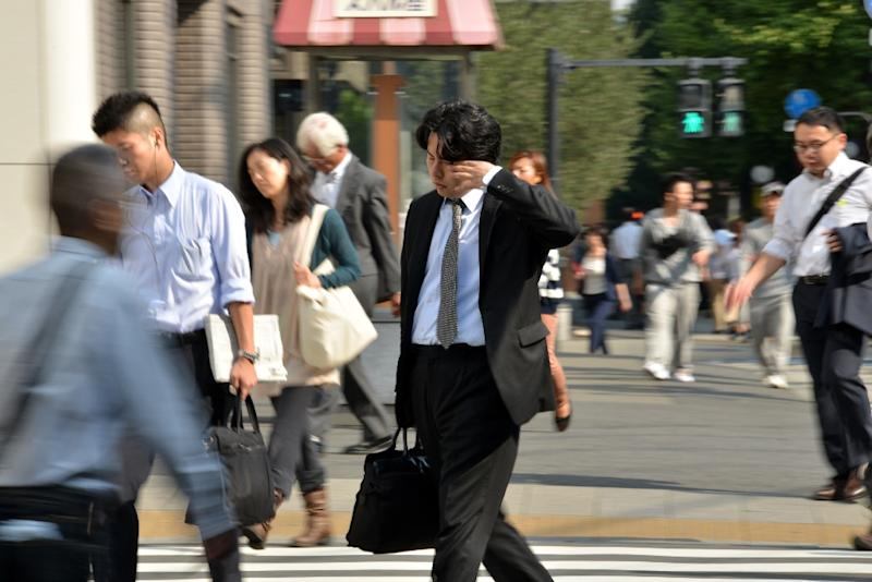This file photo shows a businessman rubbing his eyes as he heads to work in Japan, where the government has released its first national employer blacklist, naming-and-shaming firms for breaching labour laws, in a bid to prevent workplace abuses