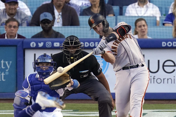 San Francisco Giants Buster Posey, right, hits a two-run home run as Los Angeles Dodgers catcher Will Smith, left, and home plate umpire Jeremie Rehak watch during the first inning of a baseball game Monday, July 19, 2021, in Los Angeles. (AP Photo/Mark J. Terrill)