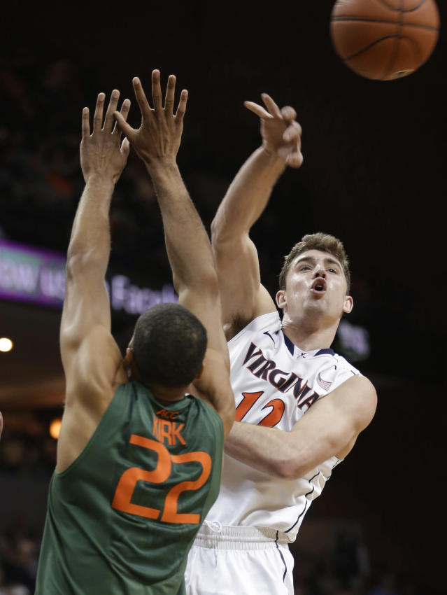 Virginia guard Joe Harris (12) makes a pass in front of Miami forward Donnavan Kirk (22) during the second half of an NCAA college basketball game in Charlottesville, Va., Wednesday, Feb. 26, 2014. Virginia won 65-40. (AP Photo/Steve Helber)