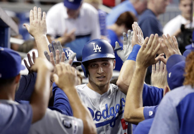 Los Angeles Dodgers' Corey Seager is congratulated after hitting a two-run home run during the first inning of the team's baseball game against the Miami Marlins, Wednesday, Aug. 14, 2019, in Miami. (AP Photo/Lynne Sladky)