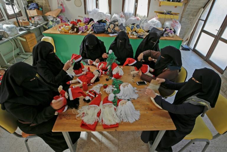 Some 20 young women are employed at the Zeina Cooperative factory in the Palestinian village of Umm al-Nasser, where they have been given three years of vocational training, learning to make gifts for a series of holidays (AFP Photo/MOHAMMED ABED)
