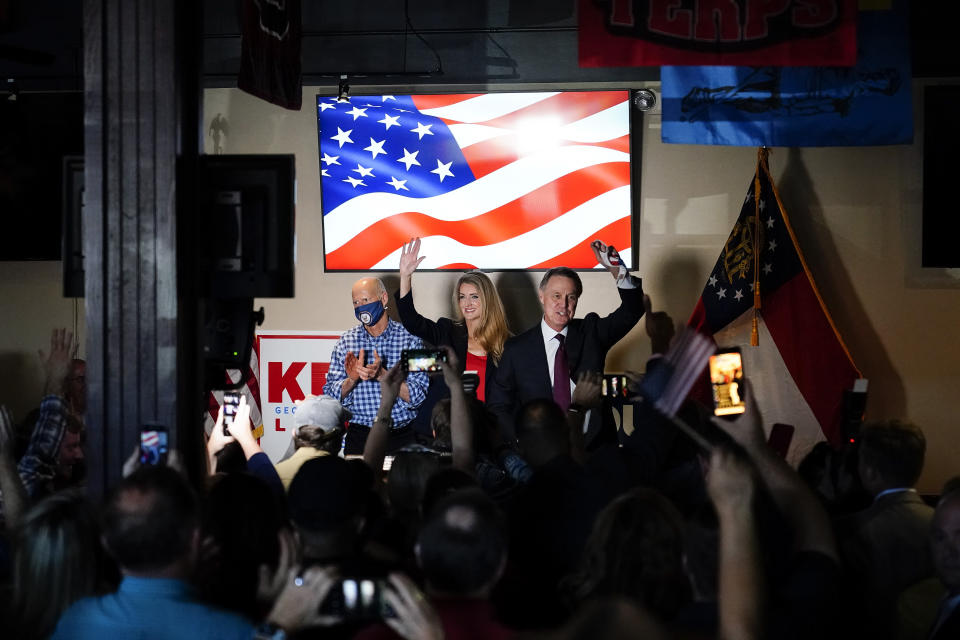 Sen. Rick Scott, R-Fla., left, Republican candidates for U.S. Senate Sen. Kelly Loeffler, center, and Sen. David Perdue wave to a crowd during a campaign rally on Friday, Nov. 13, 2020, in Cumming, Ga. (AP Photo/Brynn Anderson)