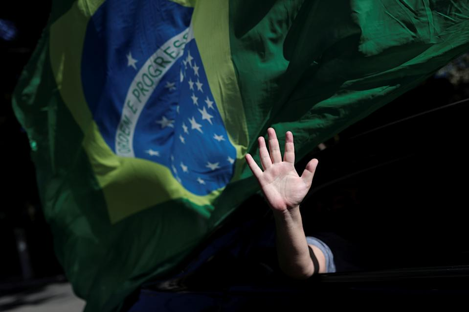 A person gestures out of a car's window as supporters of Brazil's President Jair Bolsonaro protest against the quarantine measures, amid the coronavirus disease (COVID-19) outbreak, in Sao Paulo, Brazil May 17, 2020. REUTERS/Amanda Perobelli     TPX IMAGES OF THE DAY