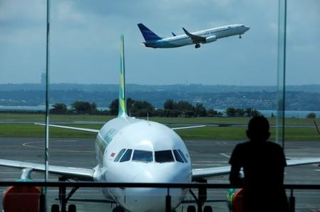 FILE PHOTO: A passenger waiting for his flight to depart watches a plane take off from the domestic terminal at Ngurah Rai International Airport, in Kuta