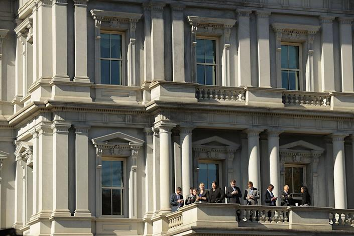 <p>Obama administration employees stand on a balcony of the Eisenhower Executive Office Building in hopes of catching a glimpse of President-elect Donald Trump's arrival at the White House on Nov. 10, 2016, in Washington, D.C. (Chip Somodevilla/Getty Images) </p>