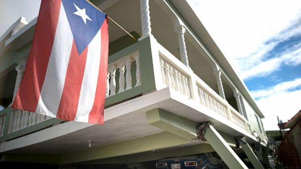 PHOTO: A Puerto Rican flag hangs from the porch of a home that collapsed on top of parked cars after an earthquake hit Guanica, Puerto Rico, Jan. 6, 2020. (Carlos Giusti/AP)