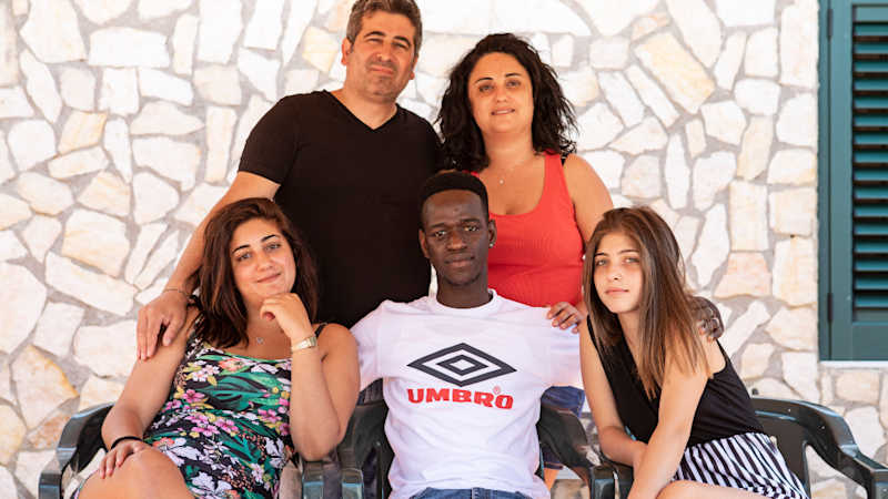 """Muhammed """"Lexy"""" Sanneh (centre) surrounded by the Ferraro family"""