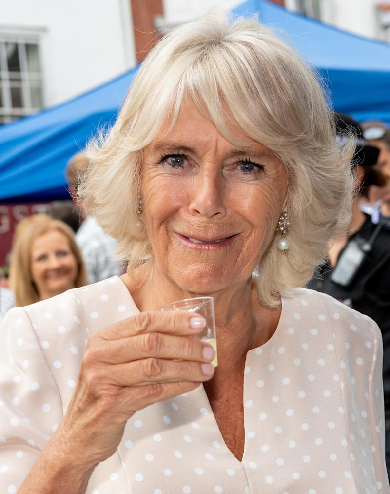 Camilla Parker Bowles preparing to take a shot of gin during a visit to a food market in Honiton, England, July 2018.