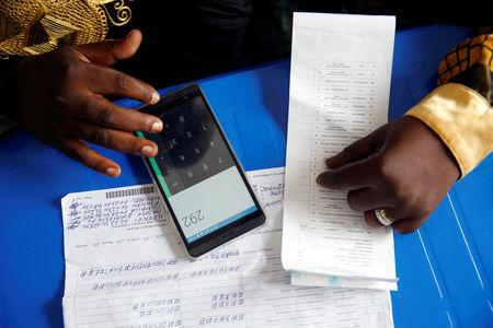 An official from Congo's Independent National Electoral Commission (CENI) uses his phone to calculate the numbers of presidential election votes at tallying centre in Kinshasa, Democratic Republic of Congo, January 4, 2019. REUTERS/Baz Ratner