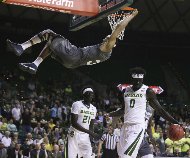 Mississippi State guard Xavian Stapleton hangs on the rim after dunking over Baylor forward Jo Lual-Acuil Jr., right, during the first half of an NCAA college basketball game in the second round of the NIT tournament, Sunday, March 18, 2018, in Waco, Texas. (Rod Aydelotte/Waco Tribune-Herald via AP)