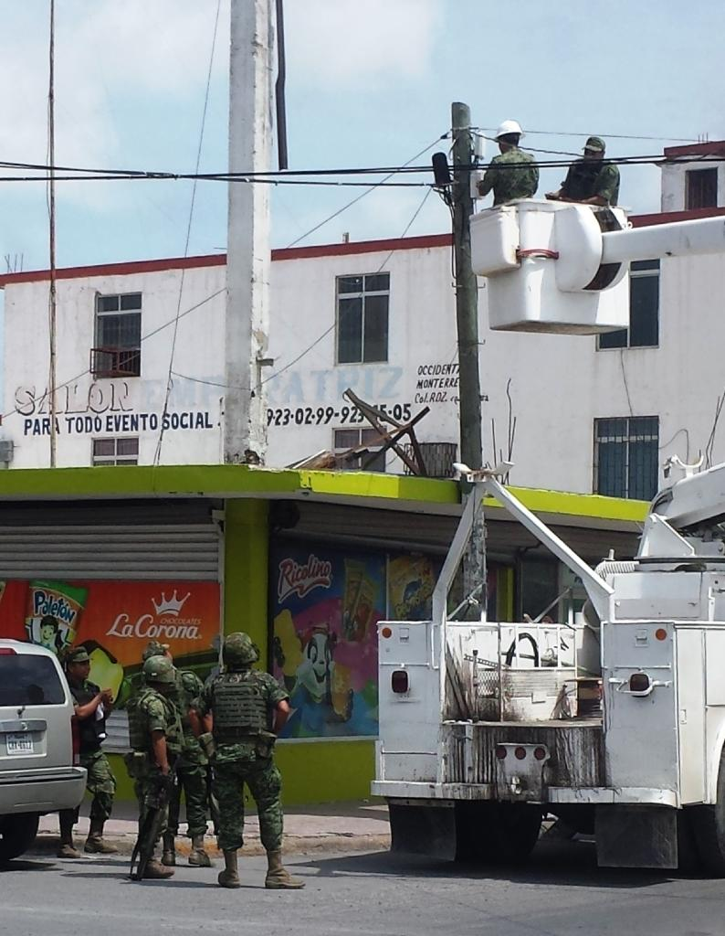 Handout picture released by Tamaulipas State Government shows members of the Mexican Army and State police dismantling video surveillance system operated by criminal group, on May 19, 2015 in the Mexican city of Reynosa