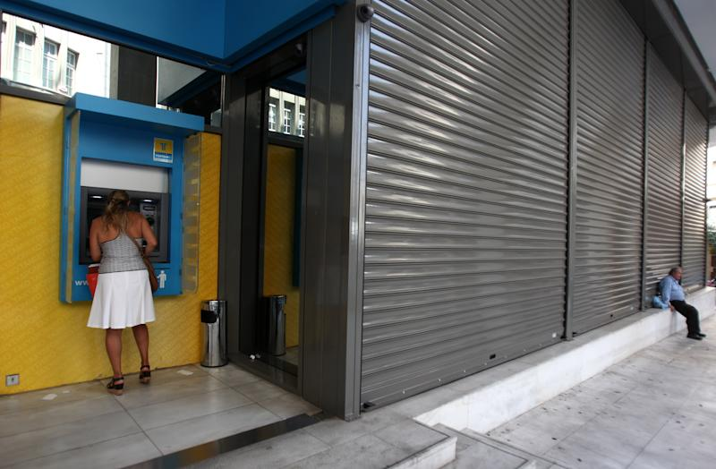 A customer at a bank machine of Hellenic Post Bank in Athens, Monday, June 30, 2012.  Bank workers on Monday held a 24-hour strike to protest cuts under Greece austerity program. (AP Photo/Thanassis Stavrakis)