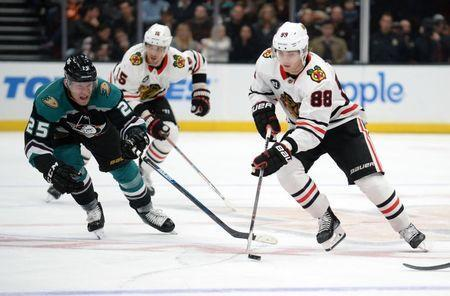 December 5, 2018; Anaheim, CA, USA; Chicago Blackhawks right wing Patrick Kane (88) moves the puck against Anaheim Ducks right wing Ondrej Kase (25) during the third period at Honda Center. Mandatory Credit: Gary A. Vasquez-USA TODAY Sports