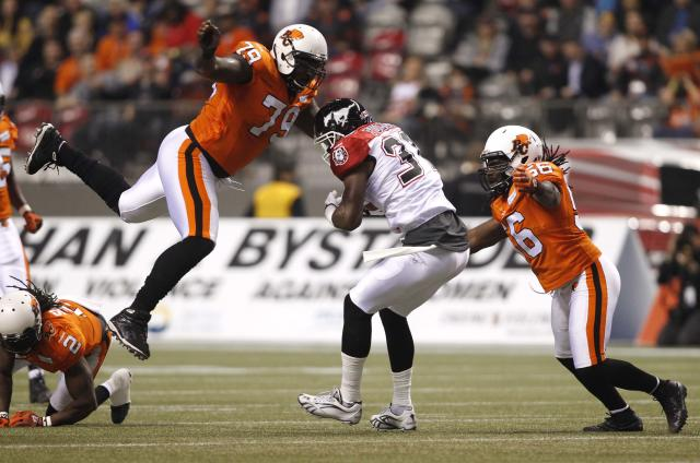 Calgary Stampeders wide receiver Jeff Fuller is tackled by B.C Lions Eric Taylor (L) and Solomon Elimimian during the first half of their CFL football game in Vancouver, British Columbia, November 1, 2013. REUTERS/Ben Nelms (CANADA - Tags: SPORT FOOTBALL TPX IMAGES OF THE DAY)