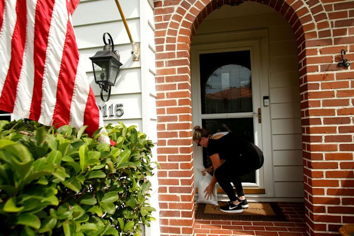 Kelly Harrington places a sandbag in front of the door of her new home.