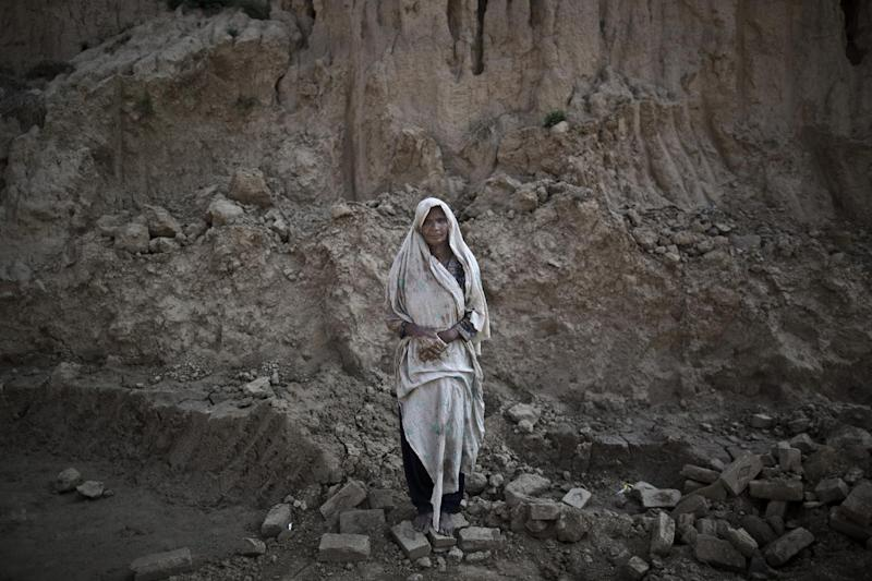 In this Sunday, March 2, 2014, photo, Amna Bhatti, 60, a Pakistani brick factory worker, poses for a picture at the site of her work in Mandra, near Rawalpindi, Pakistan. Amna is in debt to her employer the amount of 150,000 rupees (approximately $1,500). (AP Photo/Muhammed Muheisen)