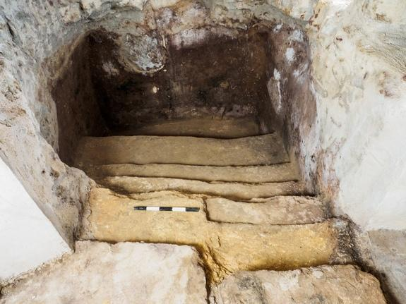 A staircase leads down to the 2,000-year-old ritual bath beneath floorboards in a family's living room.