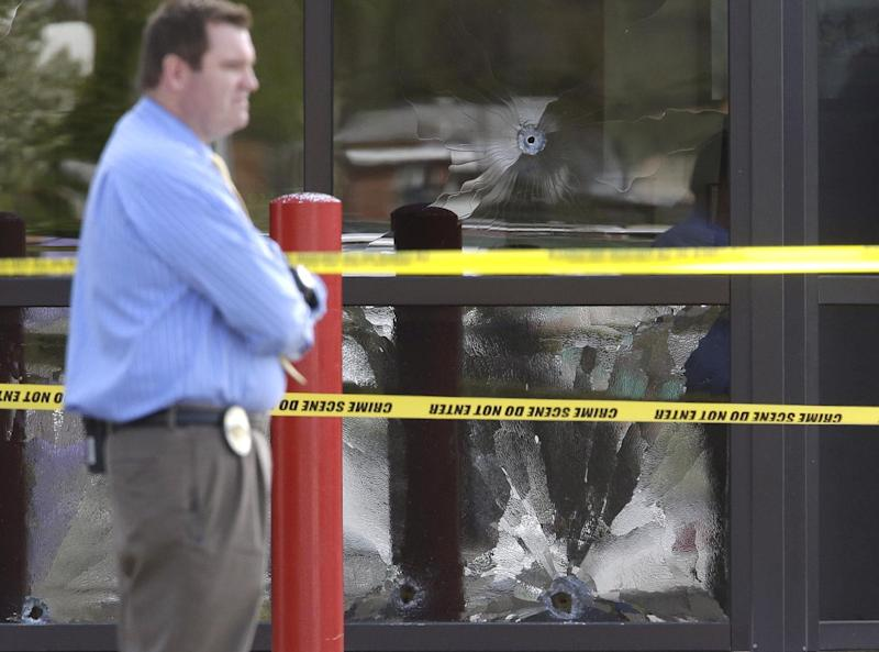 A West Valley City Police Officer stands near a bullet shattered window at the West Valley City Police Department Monday, April 29, 2013, in West Valley City, Utah. Authorities in a Salt Lake City suburb say a man shot after pulling a gun in a police lobby told officers months ago that he wanted to be shot by police. West Valley City police Sgt. Jason Hauer says the man shot Monday morning was 39-year-old James Ramsey Kammeyer. Hauer says Kammeyer entered the lobby around 8:30 a.m. Monday and asked an officer to come out from behind a partition. When several officers came to help, Kammeyer pulled out a gun and at least one of the officers shot him multiple times. (AP Photo/Rick Bowmer)
