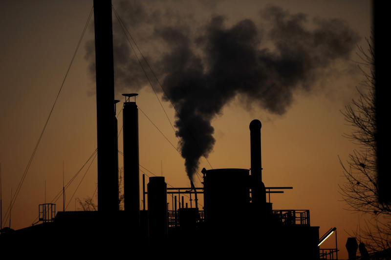 FILE - In this Friday, Dec. 14, 2018 filer, smoke billows from a chimney of a factory, in Ospiate, near Milan, Italy. The eurozone's third-largest economy and a major exporter, Italy on Wednesday becomes the first western industrialized nation to idle swaths of industrial production to stop the spread of coronavirus by keeping yet more of the population at home. The new coronavirus causes mild or moderate symptoms for most people, but for some, especially older adults and people with existing health problems, it can cause more severe illness or death. (AP Photo/Luca Bruno, File)