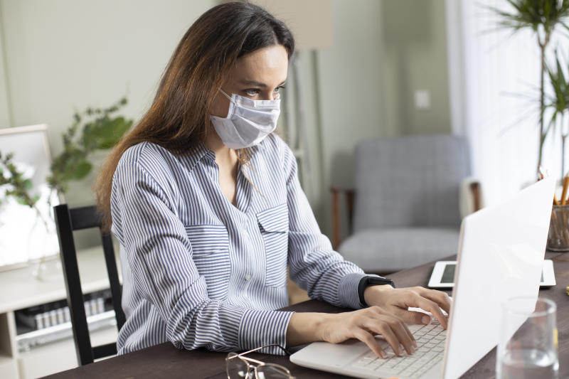 Business woman with mask working in the office on laptop. Concept, contagious disease, coronavirus.