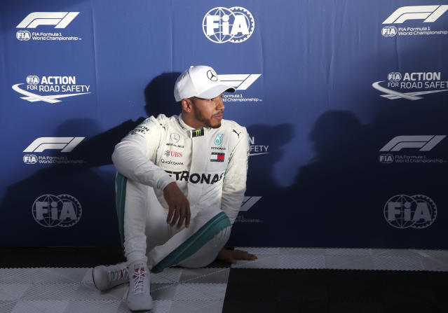 Mercedes driver Lewis Hamilton of Britain sits on the ground after qualifying at the Australian Formula One Grand Prix in Melbourne, Saturday, March 24, 2018. Hamilton has poll ahead of Ferrari driver Sebastian Vettel of Germany and Ferrari driver Kimi Raikkonen of Finland. (AP Photo/Rick Rycroft)