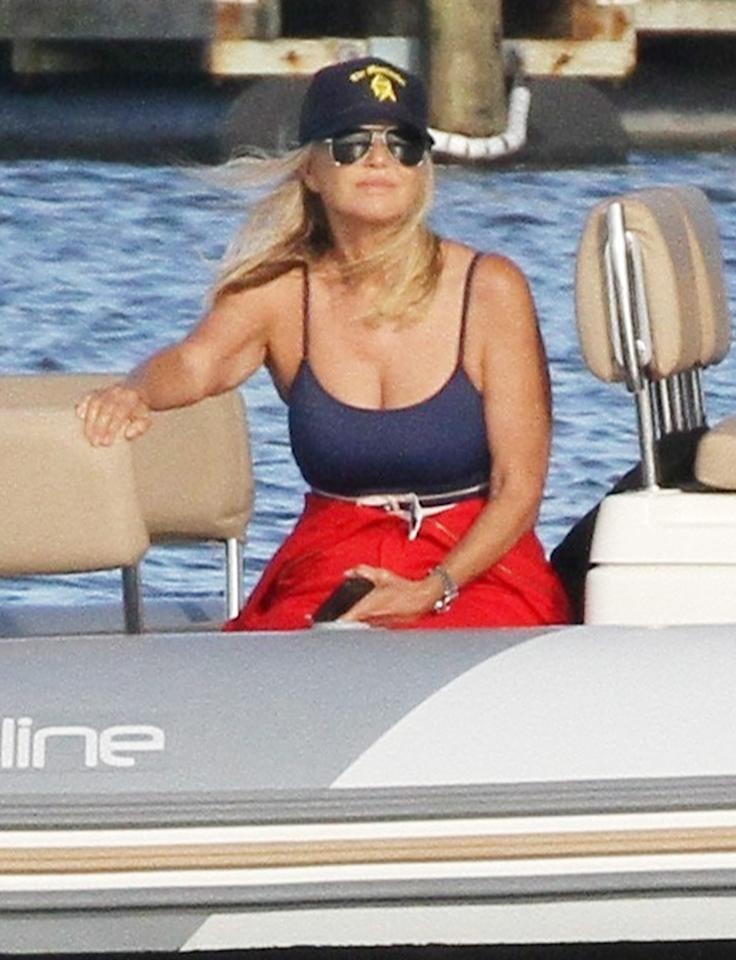 <p>Christie Brinkley hangs out on a boat on a sunny Monday, wearing a blue suit and a red jumpsuit wrapped around her waist.</p>