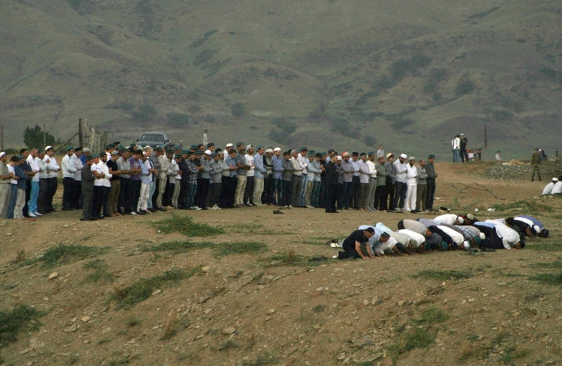 In this photo taken Tuesday, Aug. 28, 2012, people mourn during funerals in Chirkei, Russia's province of Dagestan. Thousands of mourners converged on a cemetery in Russia's republic of Dagestan on Tuesday night for the burial of Said Afandi, a leader of Sufi Muslims in the region, and five of his followers, who were killed by a female suicide bomber in an attack at Afandi's home in the village of Chirkei. (AP Photo/Abdula Magomedov/ NewsTeam)