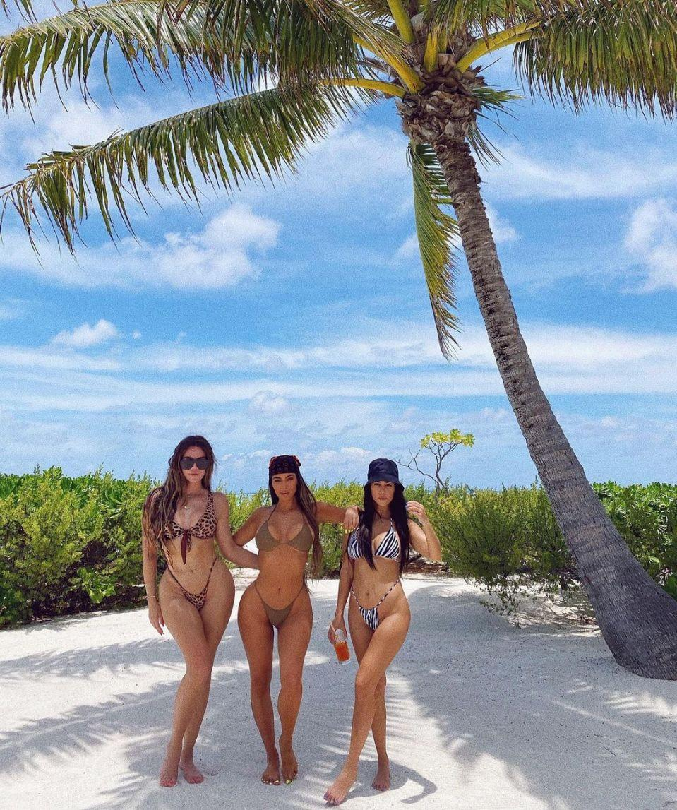 Kim Kardashian, Kourtney Kardashian and Khloe Kardashian wearing bikinis on the beach