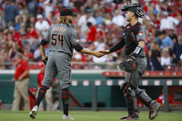 Arizona Diamondbacks relief pitcher Jimmie Sherfy, left, celebrates with catcher Carson Kelly, right, after closing the ninth inning of a baseball game, Saturday, Sept. 7, 2019, in Cincinnati. (AP Photo/John Minchillo)