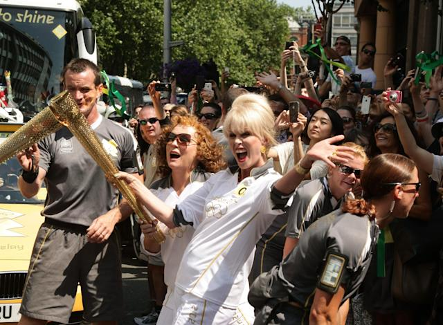 British actresses and torchbearers Joanna Lumley, center right, and Jennifer Saunders, center left, carry the Olympic Flame on the Torch Relay leg between Lambeth and Kensington and Chelsea, in London, Thursday, July 26, 2012. The opening ceremonies for the 2012 Summer Olympics will be held Friday, July 27. (AP Photo/LOCOG,Gareth Fuller)